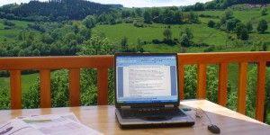 Travail sur ordinateur depuis le balcon d'un chalet